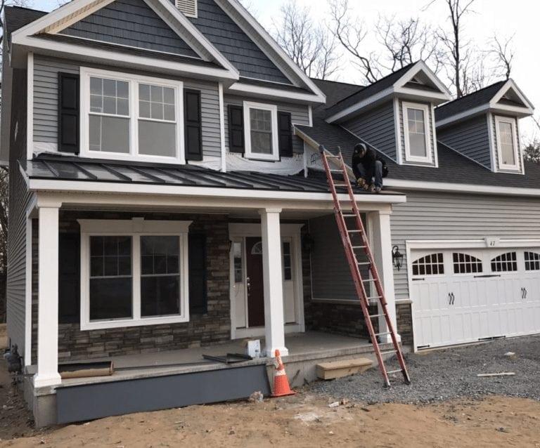 infinite roofing crewmember installing metal roof skirting
